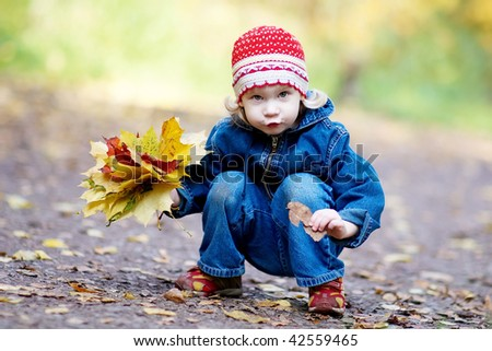 The girl with yellow leaves in autumn wood