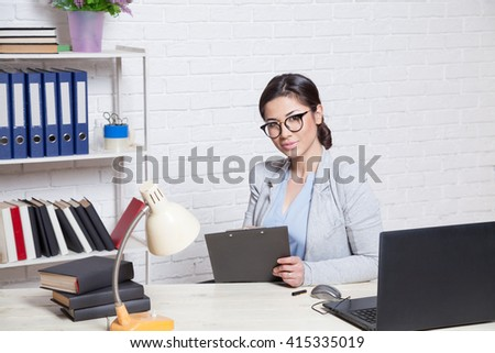 the girl works in an Office at a computer