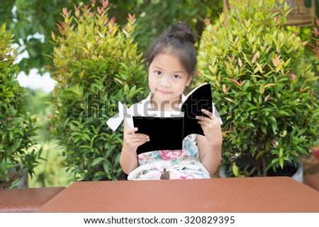 The girls are reading a book by the cover of a black background. - stock photo