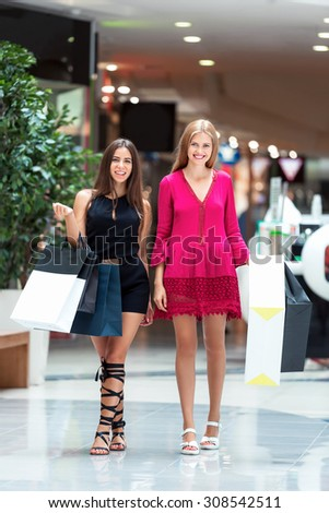 The girls enjoy shopping in the store. It's a very happy day - stock photo