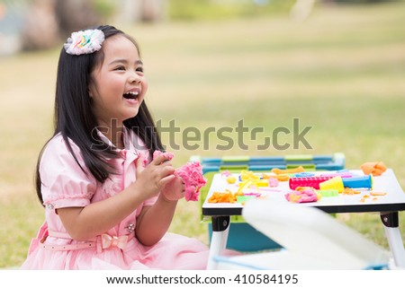 The girls enjoyed playing with clay , play out door - stock photo