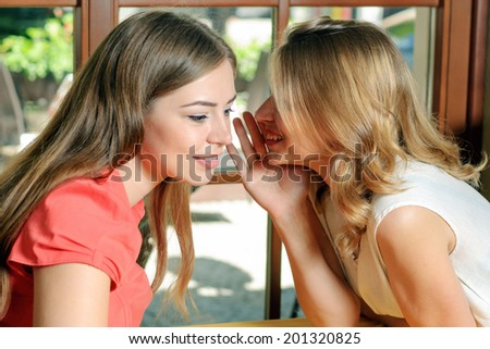 The girls whisper in cafe. Blonde brunette whispering a secret. - stock photo