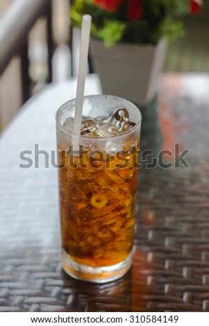 the glass of black aerated soft drink on the table