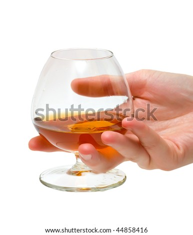 The glass of brandy in female hand. Isolated. - stock photo