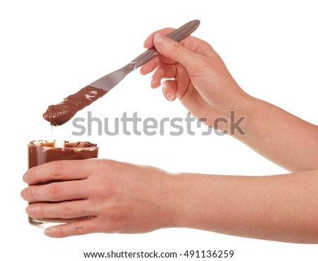 The glass of chocolate cream and a knife in the hands of women isolated on white background.