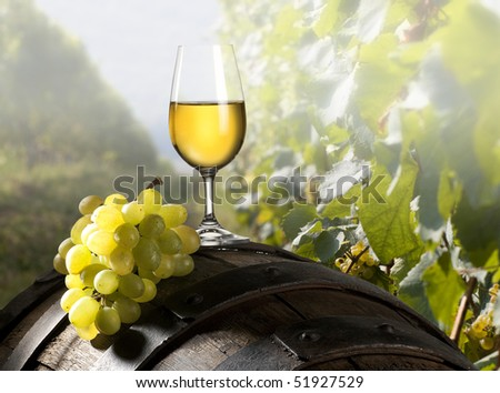 The glass of wine an and old barrel and grape - stock photo