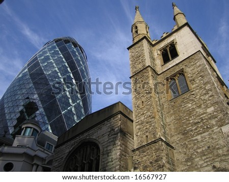 The glass offices of the Swiss Re Gherkin rising from behind historic stone church, City of London, England uk - stock photo