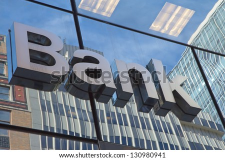 The glass wall of the building with the inscription Bank - stock photo