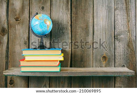 The globe and multi-coloured books on a wooden shelf. On a wooden background. - stock photo