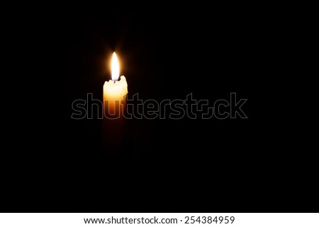 The glowing candle's image is isolated against a black background and fades into a shadow.  - stock photo