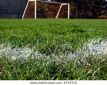 the goal of a soccer field viewed from the corner of the large box. Focus on the white markings. - stock photo