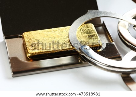 The gold bar put in the metal name card box and chrome metal handcuffed represent the crime and business with finance concept related idea.