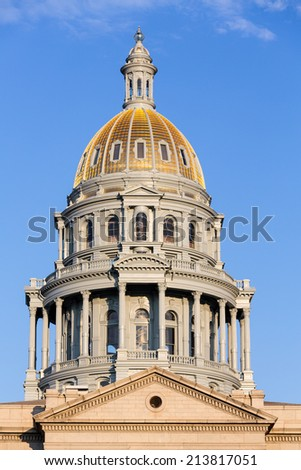 The gold leaf covered dome of the State Capitol Dome in Denver Colorado shortly after sunrise - stock photo
