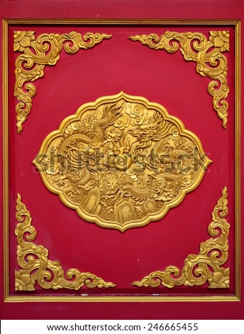 The golden dragon on the red door of Chinese temple in Thailand