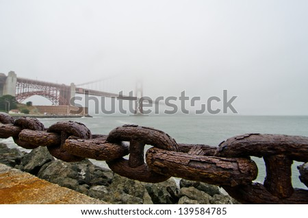The Golden Gate Bridge as seen from behind a railing chain at the Presidio. - stock photo