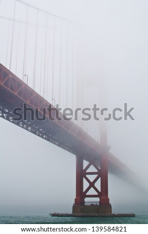 The Golden Gate Bridge disappears into the fog. - stock photo