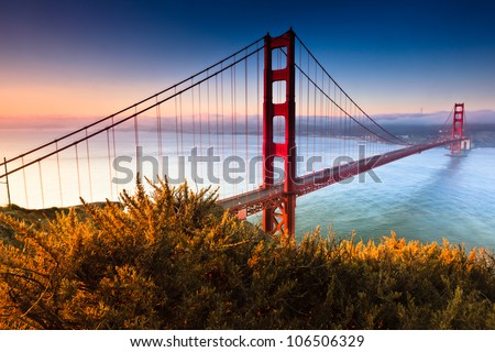 The Golden Gate Bridge of San Francisco, California basks in the warm colorful foggy light of an early morning. - stock photo