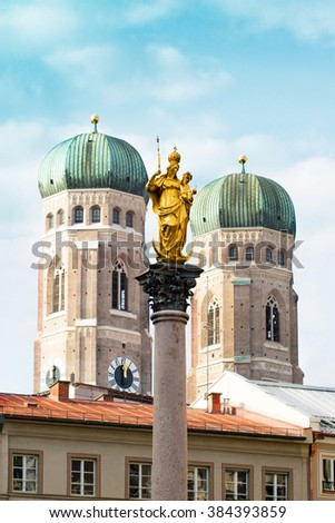 The Golden Mary's Column opposite the towers of the Cathedral of Our Dear Lady in Marienplatz in Munich, Germany, at daytime. - stock photo
