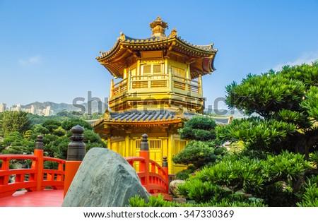 The Golden pavilion and red bridge in Nan Lian Garden near Chi Lin Nunnery, famous landmark in Hong Kong - stock photo