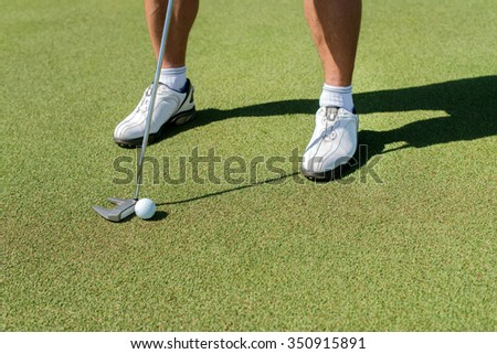 The golf day. Golfer holding a a club and is going to hit the golf ball. - stock photo