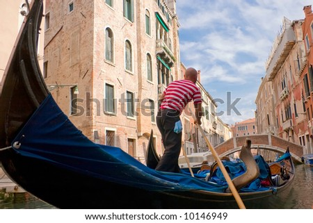 The gondolier floats on the channel of Venice - stock photo