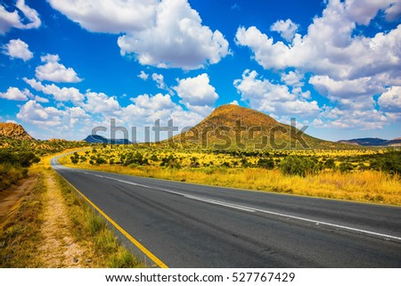 The good asphalt highway in Namibia. Fluffy clouds over the savannah. Along the road low trees and yellowed grass