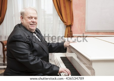 The good-natured charming aging musician resting behind a white piano