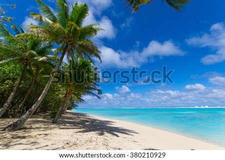 The gorgeous turquoise sea of Rarotonga lagoon viewed from white sandy beach under coconut palm tree shadow. Cook Islands, South Pacific Ocean. - stock photo