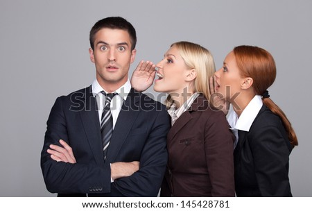 The gossip line. Two beautiful young businesswoman telling gossips to the businessman - stock photo