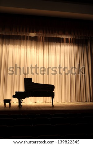The grand piano on the brown curtain background - stock photo