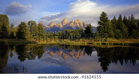 The Grand Teton Mountain Range reflecting in a beaver pond at Schwabackers Landing in Grand Teton National Park, located in Wyoming. - stock photo