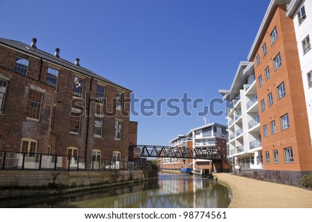 the grand union canal running through old wolverton district of milton keynes in buckinghamshire england, an area of urban regeneration with apartment blocks facing victorian industrial buildings - stock photo