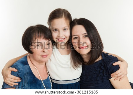 The granddaughter embraces the grandmother and mother on a white background - stock photo