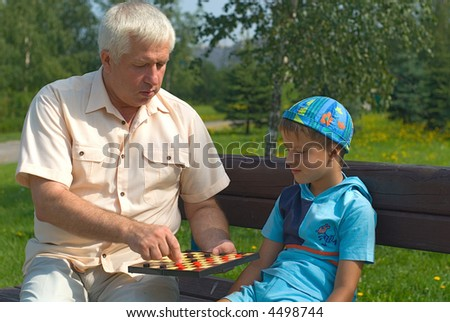 The grandfather and grandson play on a bench in park - stock photo