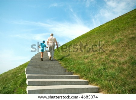 The grandfather and grandson walk in park
