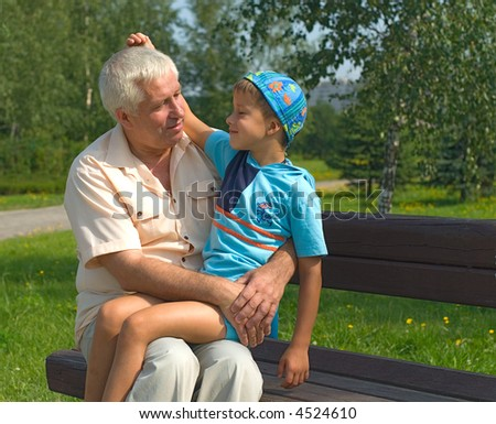 The grandfather holds grandson in a lap park