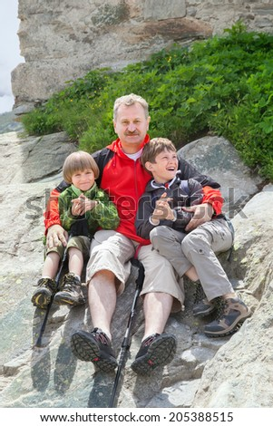 the grandfather of two grandsons resting on the rocks in the mountains - stock photo