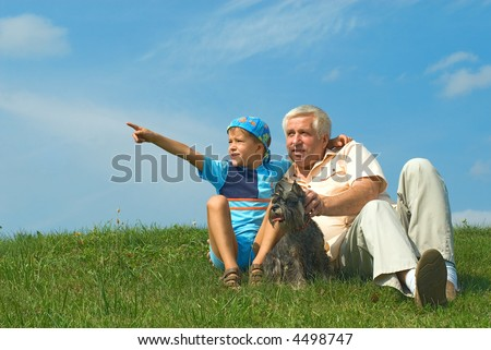 The grandfather with grandson and a dog look in distance - stock photo