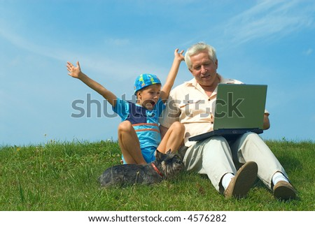 The grandfather with grandson sit on a green grass