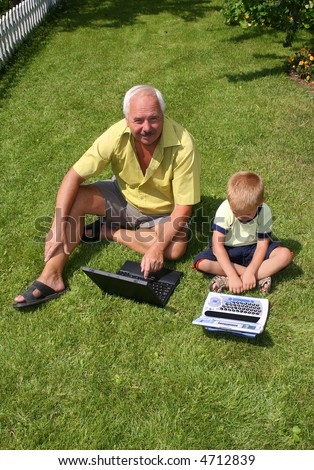 The grandfather with grandson sit on a green grass - stock photo