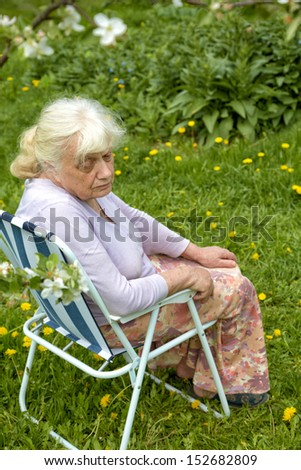 The grandmother in  garden under a blossoming apple-tree