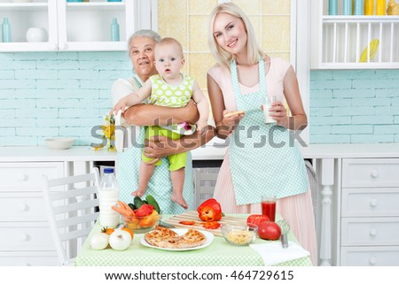 The grandmother the young girl and the small child in kitchen near a table on which pizza lies.