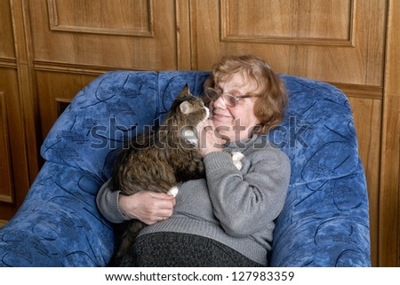 The grandmother with a cat in house conditions - stock photo