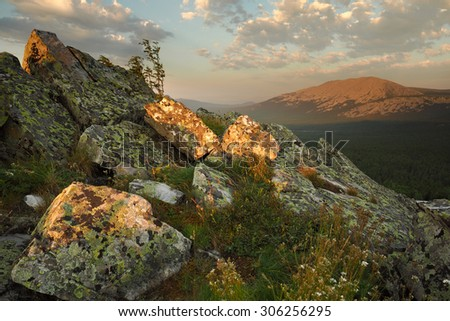 The granite boulders on the backdrop of the Big Iremel mountain in the morning light in summer, South Urals, Russia. - stock photo