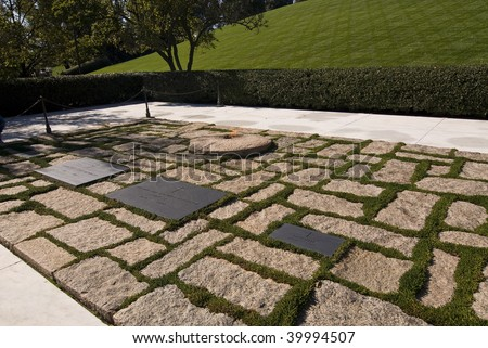 The grave stones of John F. Kennedy and his wife Jacqueline Kennedy Onassis at Arlington National Cemetery. - stock photo