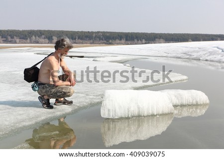 The gray-haired man with a naked torso the considering ice on the thawing river in the spring