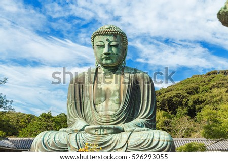 The Great Buddha in Kamakura Japan which is surrounded by green leaves.