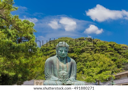 The Great Buddha in Kamakura, which is surrounded by green leaves.