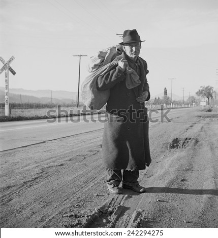 The Great Depression. Itinerant worker, traveling by foot, looking for work in mines, lumber camps, or farms. Industrial Workers of the World (IWW). Photo by Dorothea Lange, 1938. - stock photo