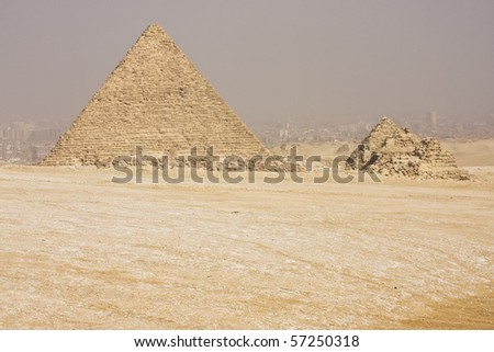 The Great Pyramid on the Giza plateau against the backdrop of a smog filled Cairo city - stock photo
